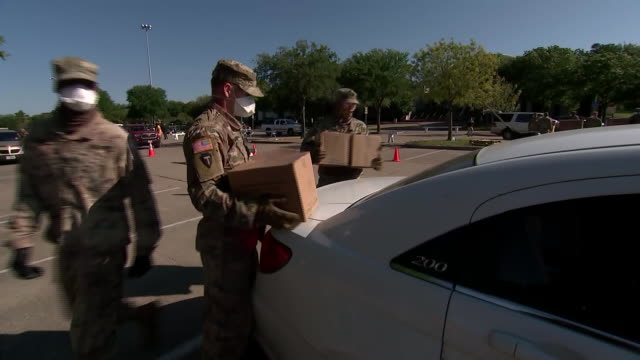 members of the national guard deliver boxes to a car at a food bank distribution area in dallas, texas during the covid-19 outbreak. - healthcare and medicine or illness or food and drink or fitness or exercise or wellbeing stock videos & royalty-free footage