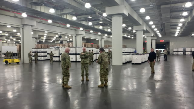 stockvideo's en b-roll-footage met members of the national guard walk through the javits convention center which is being turned into a hospital to help fight coronavirus cases on... - krijgsmacht