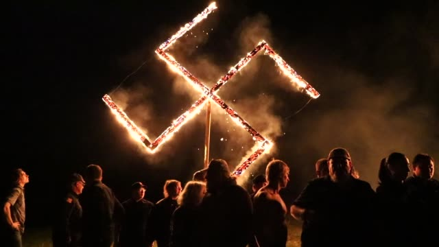 stockvideo's en b-roll-footage met members of the national socialist movement one of the largest neonazi groups in the us hold a swastika burning after a rally on april 21 2018 in... - racisme