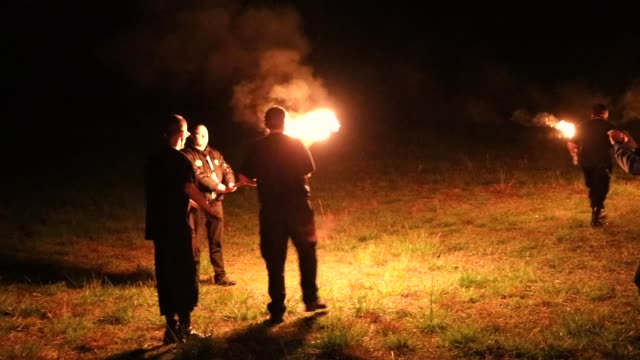 stockvideo's en b-roll-footage met members of the national socialist movement, one of the largest neo-nazi groups in the us, hold a swastika burning after a rally on april 21, 2018 in... - nazism