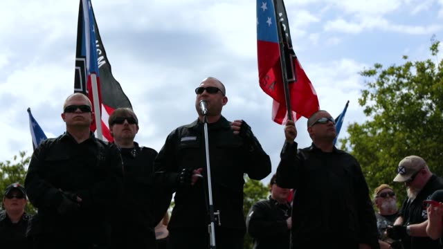 vídeos de stock e filmes b-roll de members of the national socialist movement one of the largest neonazi groups in the usduring a rally on april 21 2018 in draketown georgia community... - comício político