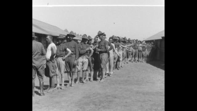 members of the nebraska national guard doing calisthenic drill / lined up and receiving typhoid inoculations / large group carrying a wooden tent... - nebraska stock-videos und b-roll-filmmaterial