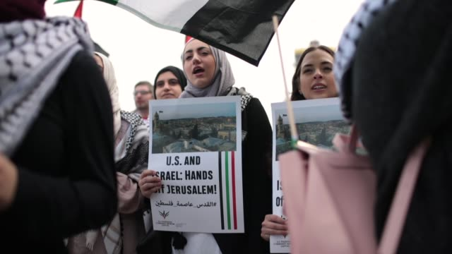 members of the palestinian community and their supporters rally and march toward the israeli consulate to protest president donald trump's decision... - embassy stock videos and b-roll footage