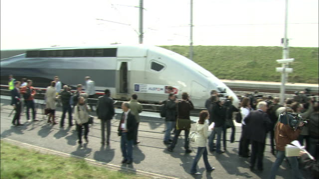 Members of the press and railway officials gather after the TGV high speed train sets a speed record in France