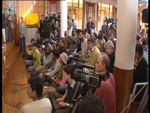 Members of the press listen to the Dalai Lama