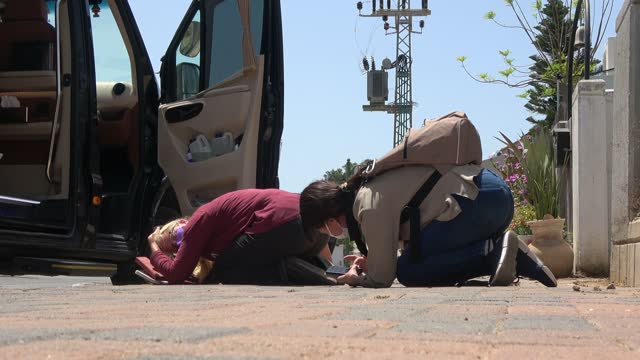 members of the press take cover on the ground as rockets are launched from the gaza strip on may 11, 2021 in ashkelon, israel. heavy exchange of fire... - striscia di gaza video stock e b–roll