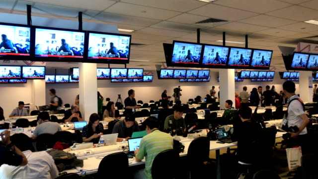 Members of the press work at the international press center under tv screens showing footage of the meeting between US President Donald Trump and...