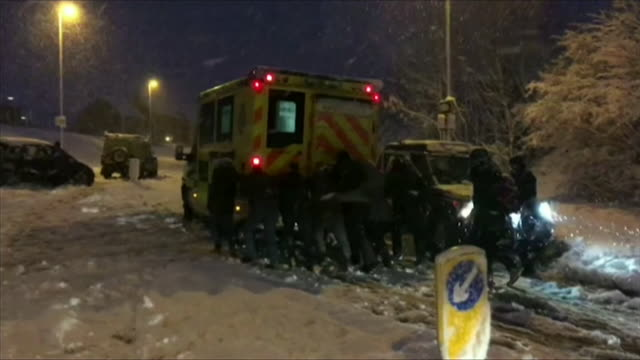 members of the public pushing ambulance up hill after it got stuck in the snow in basingstoke - uphill stock videos & royalty-free footage