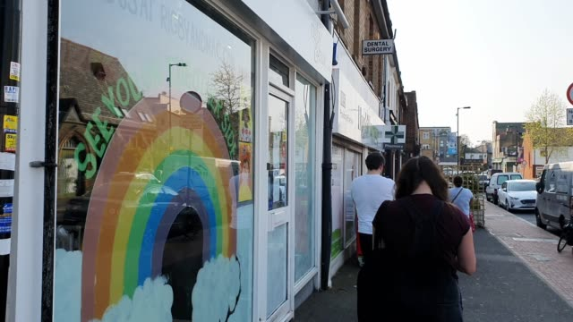 members of the public queue outside a chemist beside a painted rainbow displayed in a shop window, which symbolises peace and hope, during the... - brian dayle coronavirus stock videos & royalty-free footage