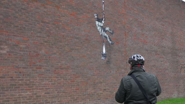 members of the public take pictures of art work by graffiti artist banksy on the side of hmp reading depicting a prisoner escaping with a typewriter,... - photographing stock videos & royalty-free footage