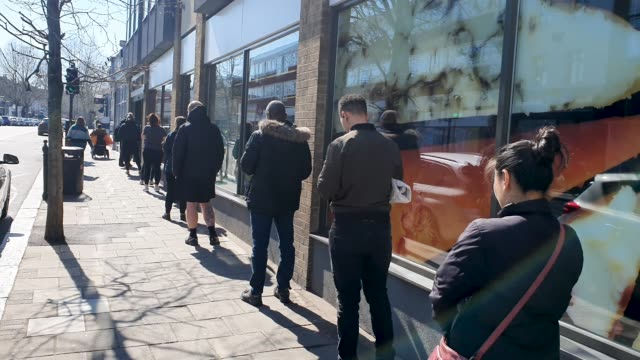 members of the public use social distancing as they queue outside marks and spencer during the coronavirus pandemic on march 25 2020 in east dulwich... - brian dayle coronavirus stock videos & royalty-free footage