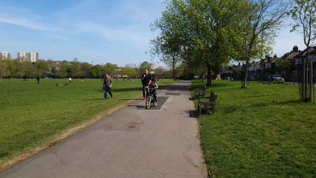 members of the public use social distancing in peckham rye park during the coronavirus pandemic on april 15, 2020 in london, england. the pandemic... - brian dayle coronavirus stock videos & royalty-free footage