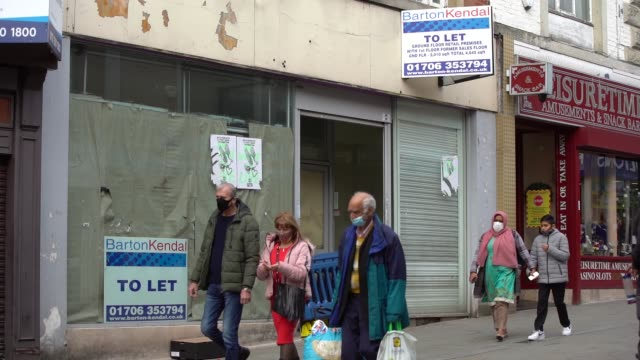 members of the public wear face coverings as they walk past a closed down detail store as greater manchester in north west of england on september 29... - face down stock videos & royalty-free footage