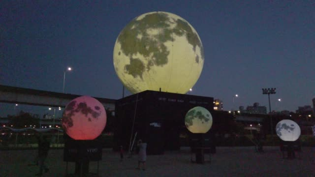 members of the public wear masks while enjoying the artificial moon to send messages of hope and overcoming the coronavirus pandemic to the people... - harvest festival stock videos & royalty-free footage