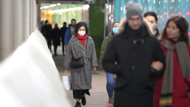 members of the public wear surgical masks as they walk around london during the coronavirus pandemic on march 17, 2020 in london, england. - mascherina chirurgica video stock e b–roll