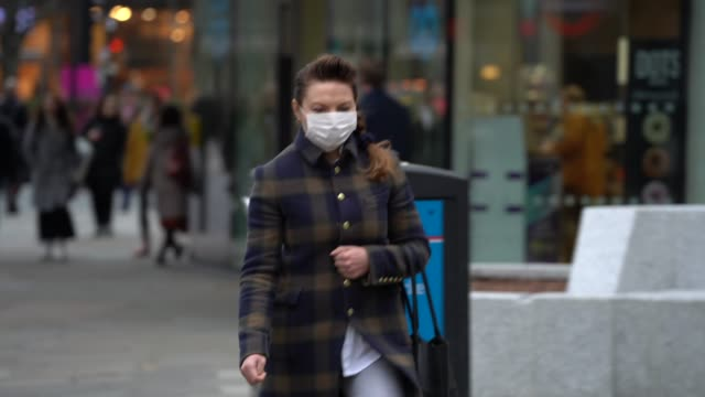 members of the public wear surgical masks as they walk around london during the coronavirus pandemic on march 17, 2020 in london, england. - protective face mask stock videos & royalty-free footage