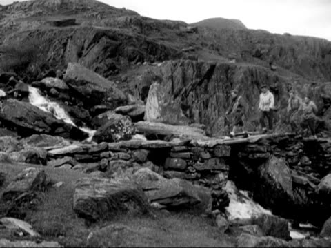 members of the raf mountain rescue team cross a stream in the snowdonia national park - snowdonia video stock e b–roll