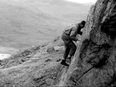 members of the raf mountain rescue team start to climb up a rockface in snowdonia - felswand stock-videos und b-roll-filmmaterial
