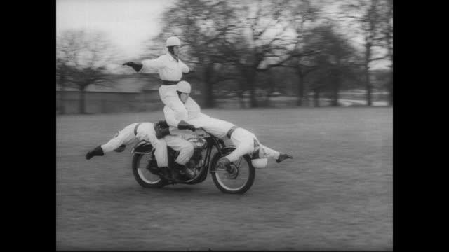 stockvideo's en b-roll-footage met members of the royal artillery aces motorcycle team crisscross in front of each other in a demonstration of skill / four men balance on one motorbike... - stunt