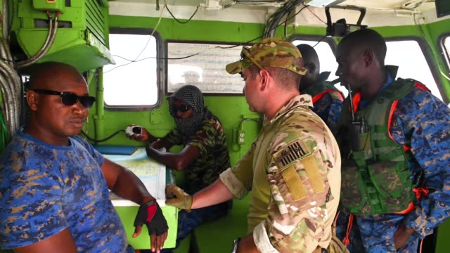 Members of the Senegalese and Gambian Navy conduct clearing techniques during a simulated drug smuggling and human trafficking scenario aboard the...