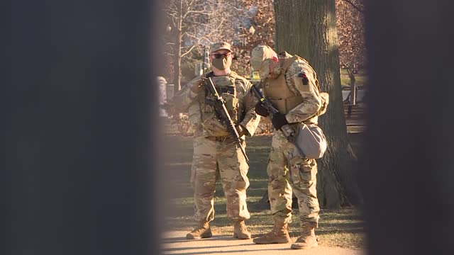 members of the us national guard stand guard in a blocked street in washington dc. washington, d.c., tightens security measures ahead of the... - 大統領就任式点の映像素材/bロール