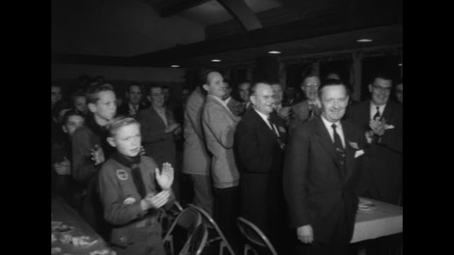 THROUGHOUT] Members of the Woodland Hills Club and guests sit at long dining tables at meeting / members guests Boy Scouts stand up from tables give...