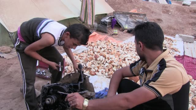 members of the yazidi community fixi engine of a car at a refugee camp for displaced people from the minority yazidi sect which were driven from... - sinjar mountains stock videos & royalty-free footage