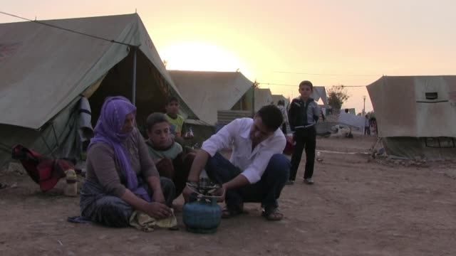 members of the yazidi community sit at a refugee camp for displaced people from the minority yazidi sect which were driven from their homes in sinjar... - sinjar mountains stock videos & royalty-free footage