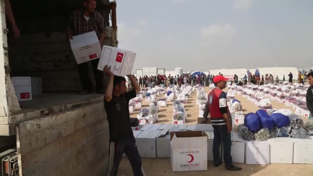 Members of Turkish Red Crescent distribute winter clothes blankets and sleeping bags to internally displaced people fled from Mosul city center at...