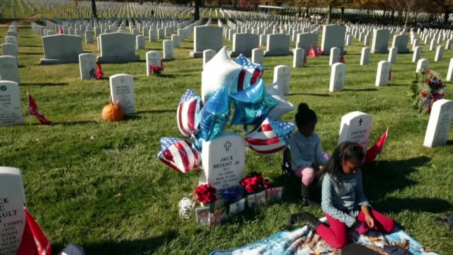 members of us army sgt jack bryant's family including nieces jayla robinson 7 and jayda souza 9 spend time at his grave on veterans day in section 60... - リース点の映像素材/bロール