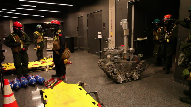 WIDE PAN members of US Marines and FDNY work in gas masks and test Andros robot