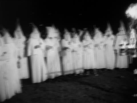 members wearing white robes standing around small burning cross / documentary - dominering bildbanksvideor och videomaterial från bakom kulisserna