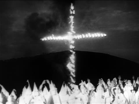 vídeos de stock, filmes e b-roll de kkk members wearing white robes standing beneath large burning cross at dusk / documentary - ku klux klan