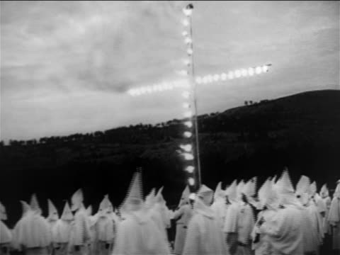 vídeos de stock, filmes e b-roll de kkk members wearing white robes walking beneath burning cross / documentary - ku klux klan