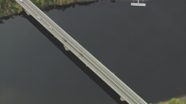 aerial memorial bridge crossing river with reflection on calm water, and traffic crossing bridge / augusta, maine, united states - augusta maine stock videos & royalty-free footage