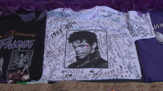 a memorial is set up on the pavement in front of the theater / items placed into the memorial include burning candles photographs of prince teeshirts... - プリンス点の映像素材/bロール