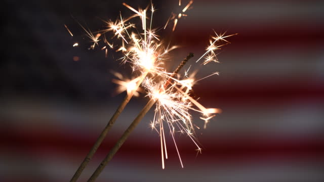 usa memorial or independence day concept with ignited sparkler in front of american flag - fourth of july stock videos & royalty-free footage