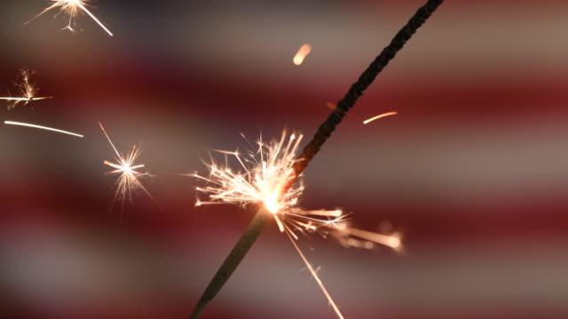 vídeos de stock, filmes e b-roll de conceito do dia do memorial ou da independência dos eua com sparkler inflamado na frente da bandeira americana - monumento comemorativo