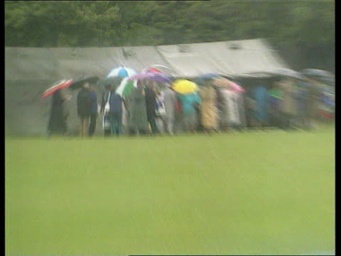 memorial service at southwick house portsmouth rain ls vets with umbrellas around entrance to tents pull out to veterans seated awaiting dday... - アロマンシェス点の映像素材/bロール