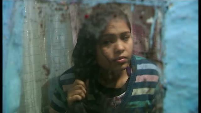 men accused of delhi gang rape to plead not guilty india delhi man along in shack jumper hanging on line people along in slum shack doorway int... - 2012年 インド集団強姦事件点の映像素材/bロール