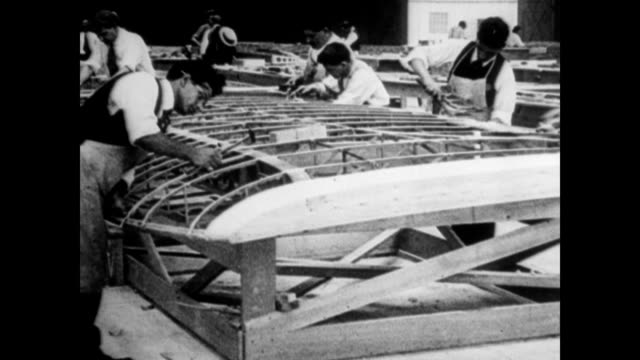 men adjusting a completed airplane / workers assembling planes / pan of the many men working on a single wing. manufacturing better planes in the... - anno 1925 video stock e b–roll