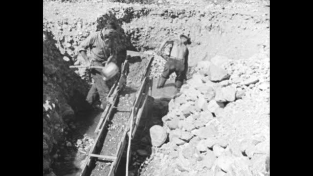 vidéos et rushes de men alongside a river shovel material from sluice into overhead, horizontal 'gutter', and a view of picturesque river / sot mrs. julius hoffman tells... - panning