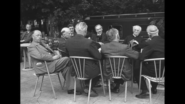 vidéos et rushes de men and a priest seated at outdoor table / note exact day not known - prêtre