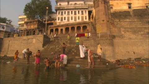 men and boys bathe in a river at the bottom of a set of stairs. - unhygienic stock videos & royalty-free footage