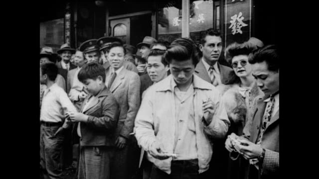 / men and boys gather in chinatown to let off firecrackers and celebrate vj day / men in suits, uniform and street clothes gathered together smiling... - chinatown stock videos & royalty-free footage