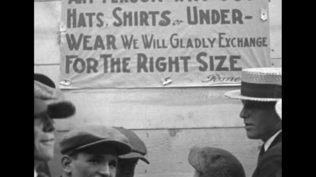 """men and boys in foreground stand in front of temporary signs tacked onto boards across store windows: """"...hats, shirts or underwear - we will gladly... - timber stock videos & royalty-free footage"""