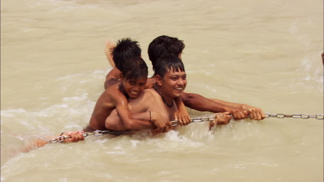 Men and boys play and wrestle in the water of the Ganges River. Available in HD.