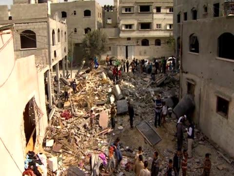 men and children walk over debris after an israeli air strike in gaza - gaza strip stock videos & royalty-free footage