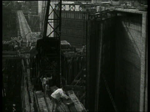 b/w men and crane building canal / no sound - canal stock videos & royalty-free footage