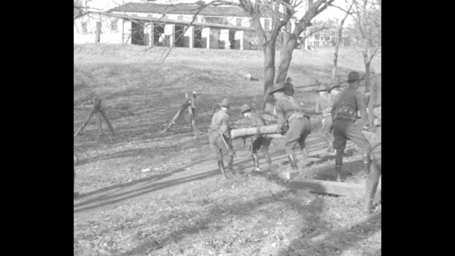 Men and horses assemble in the cold and soldiers run to area with depression and build wooden trestle which horses and a wagon pass over trestle took...